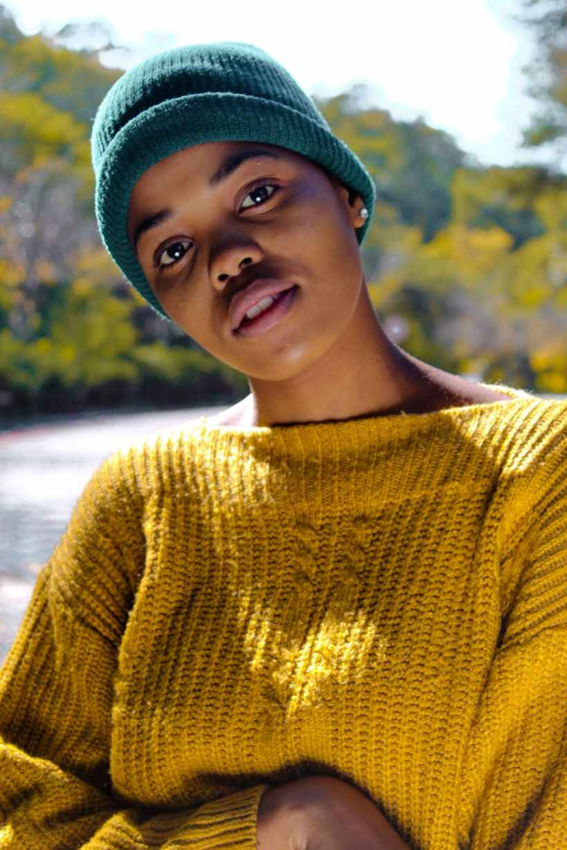 woman wearing yellow knit sweater and blue knit hat